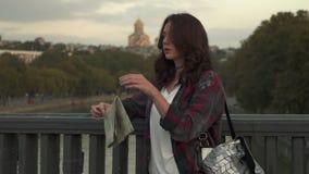 Jovem mulher bonita com o mapa do turista que olha ao redor na rua da cidade filme