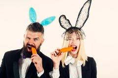 Jovem mulher bonita com orelhas do coelho e o cartaz vazio no fundo da cor Apronte para o partido Easter feliz fotos de stock