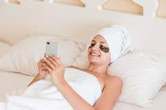 Jovem mulher bonita com os remendos inferiores do olho e telefone celular da utiliza??o no roup?o que encontra-se na cama Menina  fotos de stock