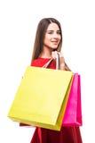 Jovem mulher bonita com os sacos shoping da cor nas mãos no fundo branco Foto de Stock