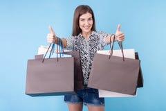 A jovem mulher bonita com pacotes está gesticulando Imagens de Stock Royalty Free