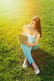 Jovem mulher bonita com a tabuleta que senta-se na grama Fotos de Stock