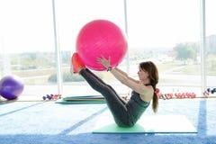 Jovem mulher bonita com treinamento da bola da aptidão no gym Conceito do estilo de vida saud?vel fotos de stock royalty free
