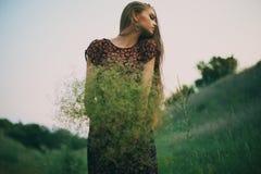 Jovem mulher bonita com um ramalhete de flores selvagens Imagens de Stock