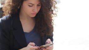 Jovem mulher bonita com um smartphone nas mãos da cidade filme