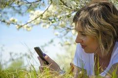 Jovem mulher bonita com um telefone, encontrando-se no campo, na grama verde e nas flores Aprecie fora a natureza Encontro de sor imagens de stock