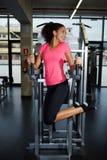 Jovem mulher bonita com uma figura delgada que exercita seus músculos abdominais imagens de stock royalty free