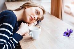 A jovem mulher bonita com uma xícara de café em um café ou em uma casa acolhedor está olhando a flor Jovem mulher ao estudar Imagens de Stock Royalty Free