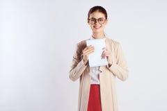 A jovem mulher bonita com vidros em um fundo claro guarda um papel, professor Imagens de Stock Royalty Free