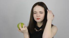 A jovem mulher bonita come uma maçã verde e sorri filme