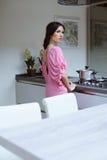A jovem mulher bonita cozinha o comensal em sua cozinha fotografia de stock royalty free