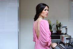 A jovem mulher bonita cozinha o comensal em sua cozinha imagens de stock royalty free