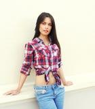 Jovem mulher bonita da forma que veste uma camisa quadriculado e calças de brim fotografia de stock