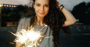 A jovem mulher bonita da raça misturada comemora com os chuveirinhos que queimam-se em suas mãos video estoque