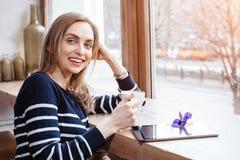 A jovem mulher bonita de sorriso da vista traseira leu o livro com a tabuleta digital perto da janela grande em um café ou em uma Fotografia de Stock