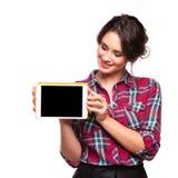Jovem mulher bonita de sorriso feliz que mostra o PC vazio da tabuleta para o copyspace fotografia de stock