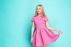 Jovem mulher bonita de sorriso no mini vestido cor-de-rosa que levanta no estúdio Fotos de Stock