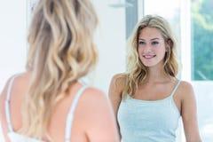 Jovem mulher bonita de sorriso que olha si mesma no espelho do banheiro fotografia de stock royalty free