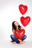 Jovem mulher bonita do dia de Valentim que veste o vestido vermelho e que guarda balões vermelhos Foto de Stock Royalty Free