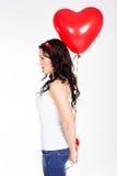 Jovem mulher bonita do dia de Valentim que veste o vestido vermelho e que guarda balões vermelhos Foto de Stock