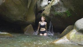 A jovem mulher bonita do movimento lento espirra na água pelas mãos no lago da montanha na floresta tropical verde com a cachoeir video estoque