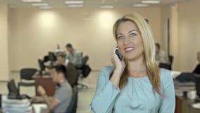 Jovem mulher bonita do retrato com cabelo branco louro na blusa azul que fala no telefone no fundo do escritório Ela que sorri filme