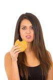 Jovem mulher bonita do retrato que levanta para a câmera que come o Hamburger ao fazer a expressão facial culpada, estúdio branco Fotos de Stock Royalty Free