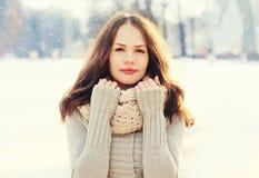 Jovem mulher bonita do retrato que veste uma camiseta e um lenço feitos malha no inverno sobre flocos de neve imagens de stock