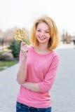 Jovem mulher bonita do ruivo que guarda o pirulito colorido Menina bonita que tem o divertimento fora Fotografia de Stock