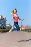 Jovem mulher bonita do ruivo que salta altamente no ar sobre o céu azul que guarda o pirulito colorido Menina bonita que tem o di Imagens de Stock