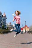 Jovem mulher bonita do ruivo que salta altamente no ar sobre o céu azul que guarda o pirulito colorido Menina bonita que tem o di Foto de Stock