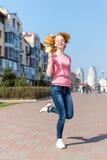 Jovem mulher bonita do ruivo que salta altamente no ar sobre o céu azul que guarda o pirulito colorido Menina bonita que tem o di Fotos de Stock Royalty Free