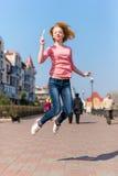 Jovem mulher bonita do ruivo que salta altamente no ar sobre o céu azul que guarda o pirulito colorido Menina bonita que tem o di Fotografia de Stock