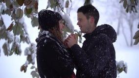 Jovem mulher bonita e homem que olham nos olhos de cada um no parque do inverno sob a neve de queda O homem aquece as mãos da sen video estoque