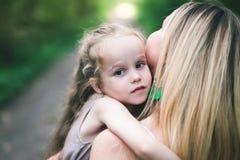 A jovem mulher bonita e sua filha pequena encantador estão abraçando foto de stock