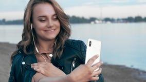 Jovem mulher bonita em olhares dos fones de ouvido vídeos de arquivo