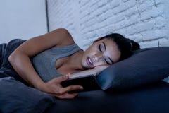 Jovem mulher bonita em seu telefone esperto tarde no asle de queda da noite imagem de stock royalty free