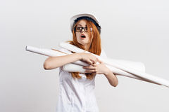 A jovem mulher bonita em um fundo claro em um capacete de segurança e em uns vidros vestindo mantém modelos, coordenador, constru fotografia de stock
