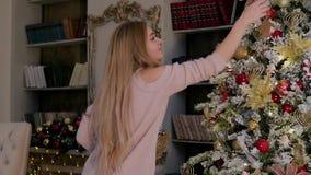 Jovem mulher bonita em um interior do Natal Vestindo uma árvore de Natal vídeos de arquivo