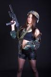 Jovem mulher bonita em um uniforme militar com um submachine gu Fotografia de Stock Royalty Free