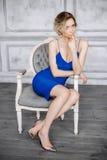 Jovem mulher bonita em um vestido azul e em umas sapatas elegantes que sentam-se em uma cadeira em um interior bonito Fotografia de Stock