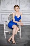 Jovem mulher bonita em um vestido azul e em umas sapatas elegantes que sentam-se em uma cadeira em um interior bonito Foto de Stock