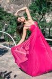 Jovem mulher bonita em um vestido de nivelamento longo que levanta na natureza, desenvolvendo o imagens de stock royalty free