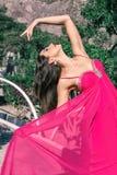 Jovem mulher bonita em um vestido de nivelamento longo que levanta na natureza, desenvolvendo o imagem de stock