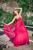 Jovem mulher bonita em um vestido de nivelamento longo que levanta na natureza, desenvolvendo o fotos de stock royalty free