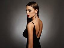 Jovem mulher bonita em um vestido 'sexy' preto que levanta no estúdio, luxo menina da morena da beleza Imagens de Stock Royalty Free