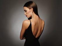 Jovem mulher bonita em um vestido 'sexy' preto que levanta no estúdio, luxo menina da morena da beleza Foto de Stock