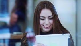 A jovem mulher bonita em uma camiseta à moda senta-se no café, bebe-se o café, usa-se a tabuleta e sorri-se felizmente cheerful vídeos de arquivo
