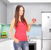 Jovem mulher bonita em uma cozinha, guardarando uma maçã Fotografia de Stock Royalty Free