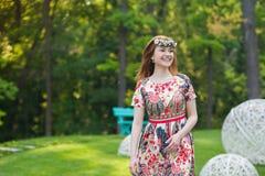 Jovem mulher bonita em uma grinalda das flores e em um vestido brilhante que senta-se no retrato na natureza, a alegria da grama  Imagens de Stock Royalty Free